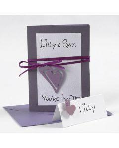 Een envelop en uitnodiging met satijnlint en hart
