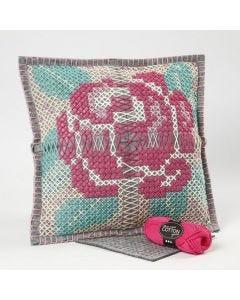 Een kussen van vilt met een geborduurde roos