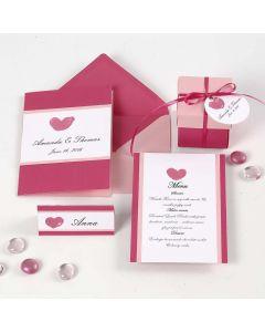 Een witte en roze uitnodiging, naamkaart, menukaart en tafel decoraties