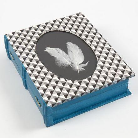Een gedecoreerde doos met een boek als omlijsting