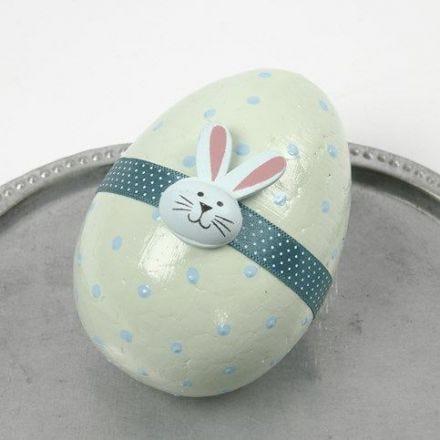 Pastel gekleurd ei met lint en houten figuur
