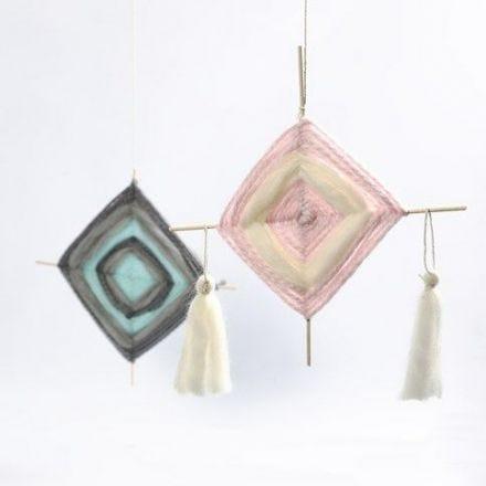 Een mobile gemaakt van bloemstokken, weefwerk en tassels