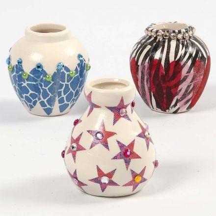 Een terracotta vaas, gedecoreerd met decoupage en strasstenen