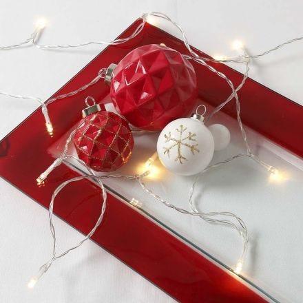 Een terracotta kerstbal met gouden lijnen in reliëf