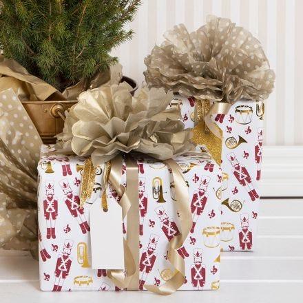 Kerstcadeau gedecoreerd met pom-pom van zijdepapier