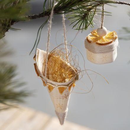 Een kegel van houtfineer versierd met gestempelde ontwerpen en natuurlijke materialen