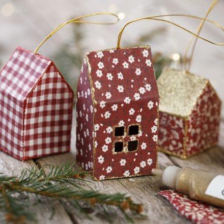 Een kersthuisje van karton bekleed met textiel en gedecoreerd met glitter