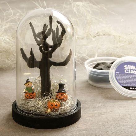 Een Halloween miniatuurwereld onder een koepelvormige stolp