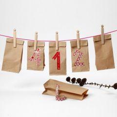 Een kerstkalender gemaakt van papieren zakken met masking tape