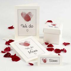 Een huwelijksuitnodiging en tafeldecoraties met harten