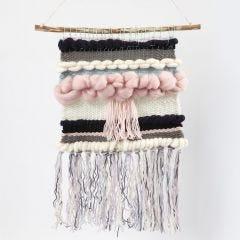 Geweven wandkleed gehangen aan een tak