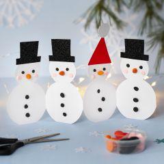 Een rij kartonnen sneeuwpoppen gedecoreerd met Silk Clay