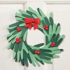 Een kerstkrans gemaakt van kartonnen handen met decoraties van Silk Clay
