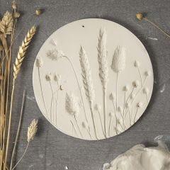 Wanddecoratie van zelfhardende klei met afdrukken van gedroogde bloemen