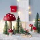 Kerstkabouter plaatst kerstboom voor zijn deur