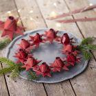 Een gevlochten kerstster met een rozenknop