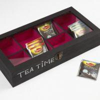 Een houten doos met glazen deksel voor theezakjes