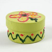 Een geverfde ronde doos met deksel, gedecoreerd met glitter