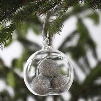 Een glazen kerstbal gevuld met kleine zilveren ballen