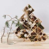 Geometrische kerstboom gedecoreerd met dennenappels, takken en licht