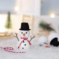 De kerstkabouter bouwt een sneeuwpop voor zijn deur