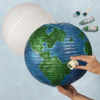 Een wereldbol van een rijstpapieren lamp gedecoreerd met acrylverf en bio-glitter