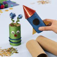 Een ruimteraket en een alien gemaakt van kartonnen kokers versierd met basis hobbymaterialen