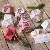 Een origami kerstbal gevouwen van origamipapier